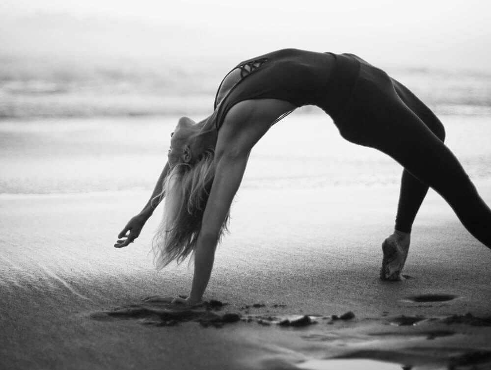 Karina practicing yoga in an arched form on the beach