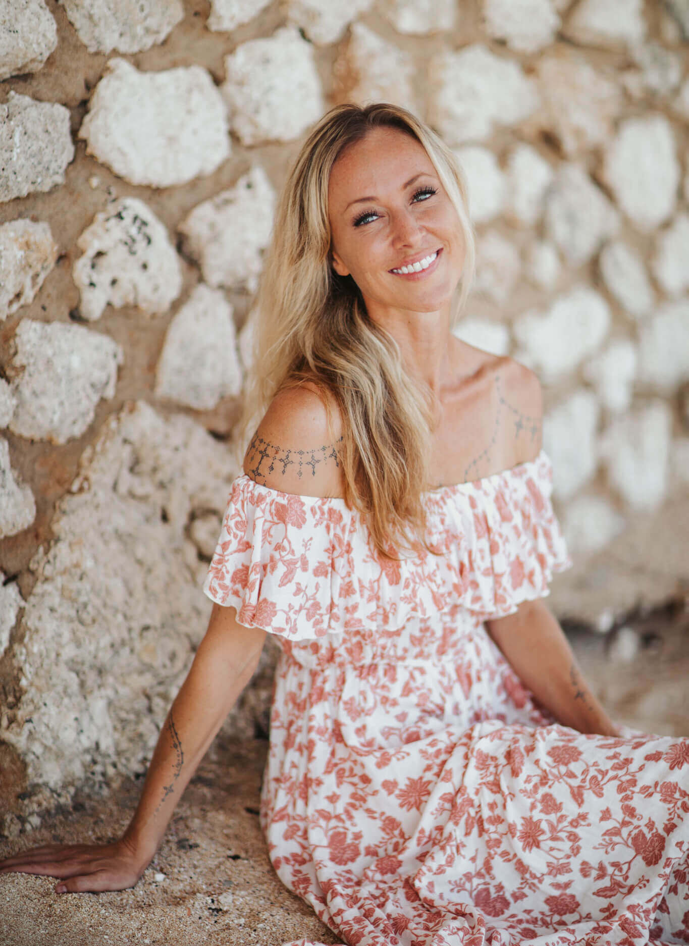 Karina smiling in floral dress sitting in front of stone wall